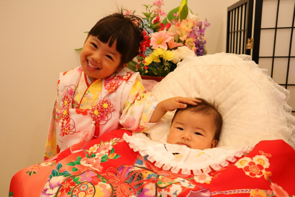 妹ちゃんの頭をなでなで。七五三とお宮参りの同時撮影。仲良し姉妹|鈴鹿|子供専門写真館スタジオバンビ|